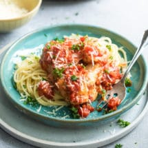 Chicken parmesan meatballs on spaghetti on a blue plate.