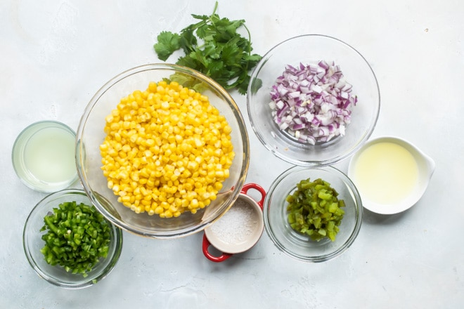 Chipotle corn salsa ingredients in clear bowls.