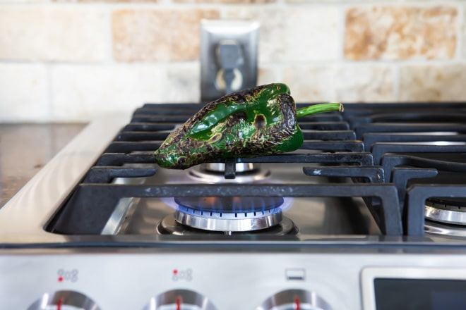 Poblano pepper being roasted on top of a stove.
