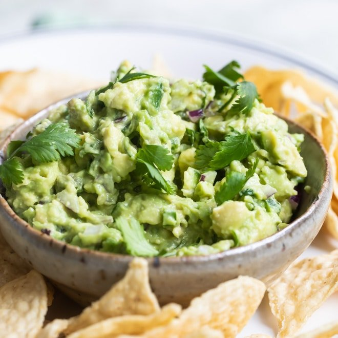 Chipotle guacamole in a bowl on a white plate with tortilla chips.