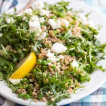 Farro salad with peas and feta on a white plate.