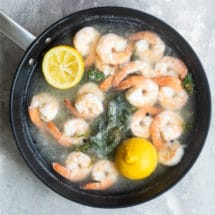 Shrimp being poached in boiling water with lemon halves in a black skillet.