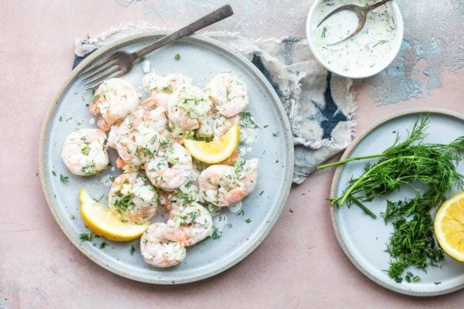 Shrimp salad on a blue plate with lemon wedges.