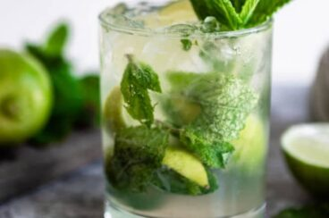 A close up of a mojito on a table with mint leaves as a garnish.