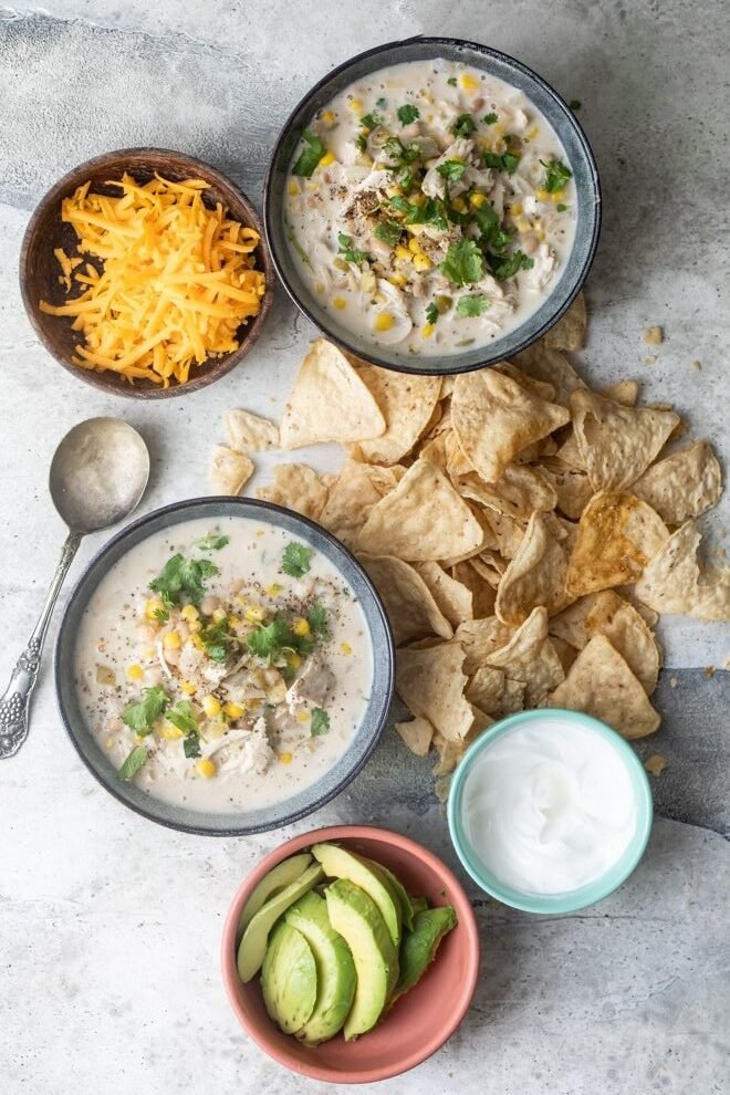 Slow cooker white turkey chili in blue bowls.