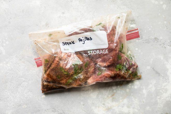 Steak being marinated in a Ziploc bag.