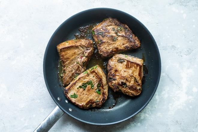 Steak searing in a black skillet.