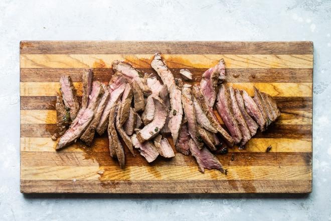 Sliced steak on a wood cutting board.
