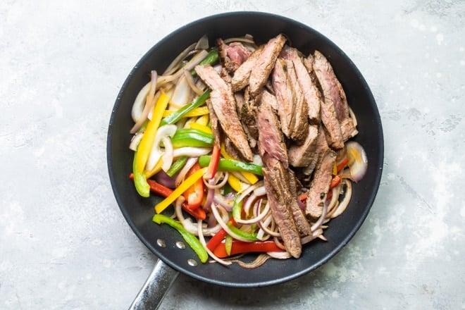 Steak and veggies in a black skillet.