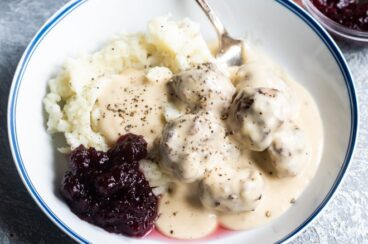 Swedish meatballs on plates with mashed potatoes, gravy, and cranberry sauce.