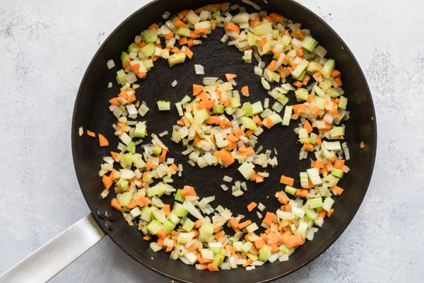 Chopped vegetables cooking in a black skillet.