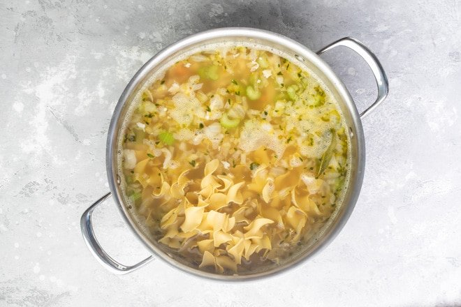 Chicken noodle soup cooking in a silver pot.