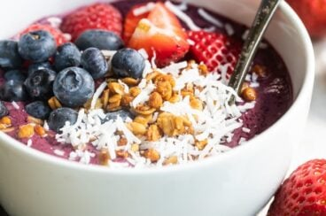 Easy acai bowl in a white bowl with a spoon.