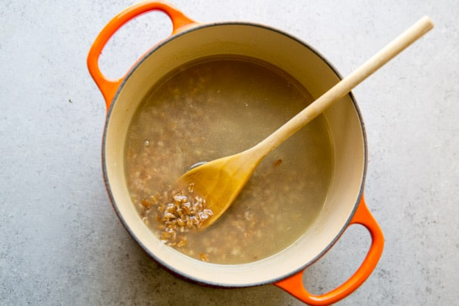 Farro cooking in water in a large pot.