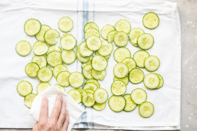 Cucumber slices being patted dry with a towel.