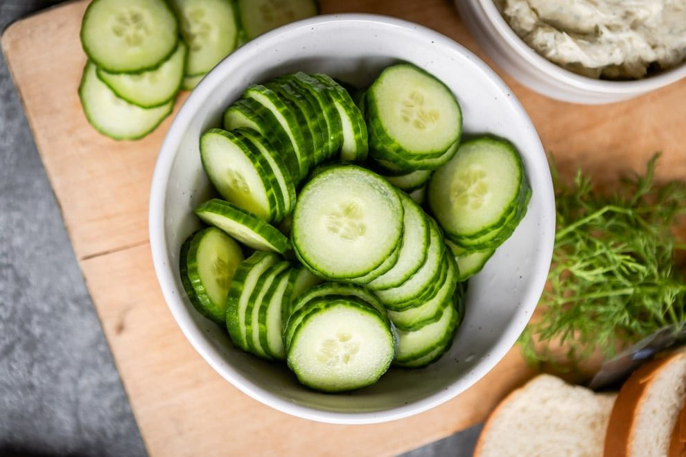 Sliced cucumbers in a white bowl.