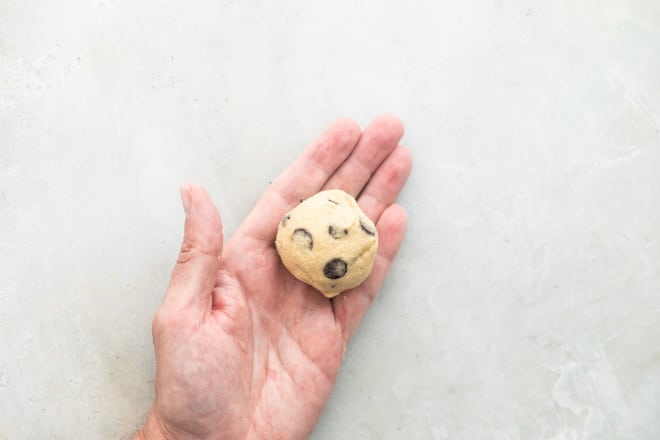 A hand holding a ball of chocolate chip cookie dough.
