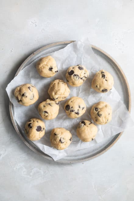 Balls of chocolate chip cookie dough on a plate before freezing.