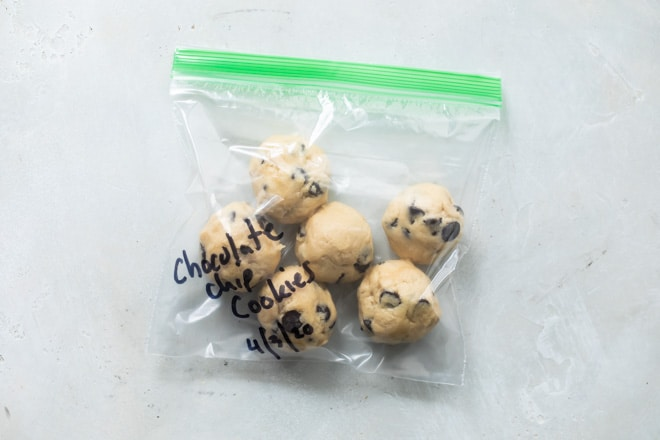 Balls of chocolate chip cookie dough in a plastic bag and labeled for the freezer.