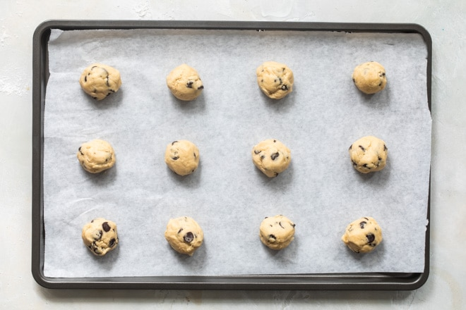 Balls of frozen cookie dough on a baking sheet before going in the oven.