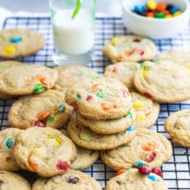 A dozen M&M cookies on a wire rack with a glass of milk and a bowl of M&Ms in the background.