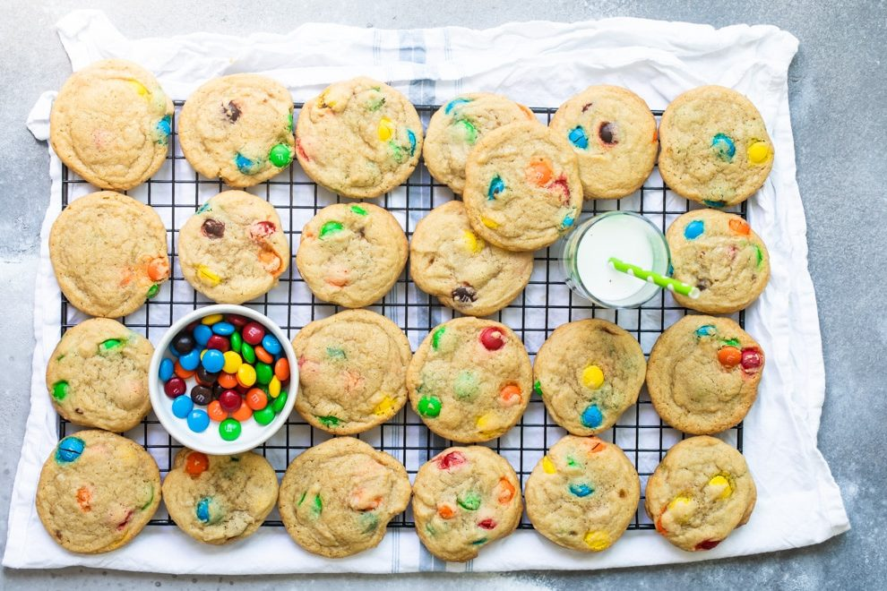 An overhead shot of a dozen M&M cookies on a wire rack with a glass of milk and a bowl of M&Ms in the background.