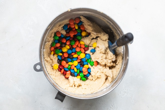 A mixing bowl with cookie dough and M&Ms sitting on it.