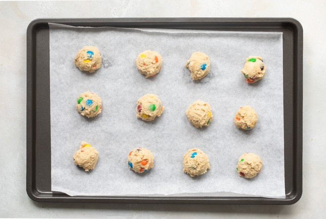 M&M cookie dough portioned and roll into balls on a baking sheet.