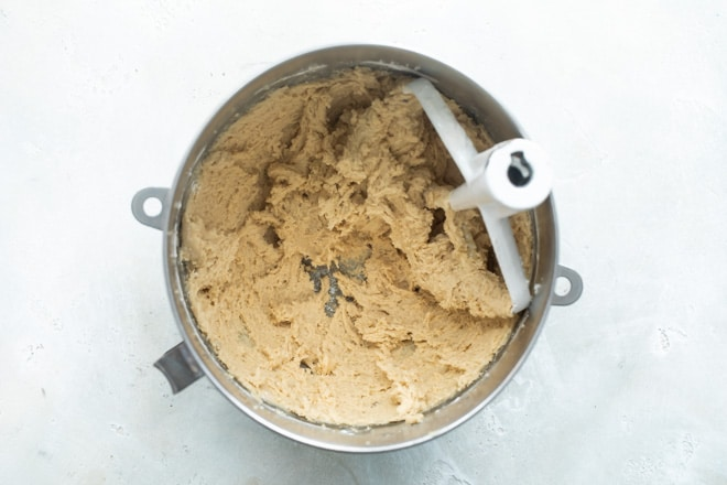 A mixing bowl with flour and other dry ingredients mixed in to the flour and sugar to make cookie dough.