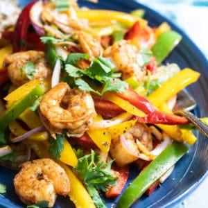 Shrimp fajitas on a blue plate.
