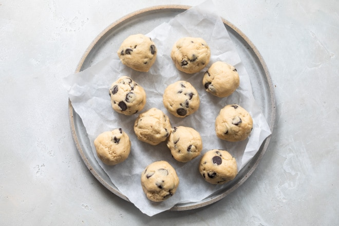 Balls of cookie dough on a round tray lined with parchment paper.