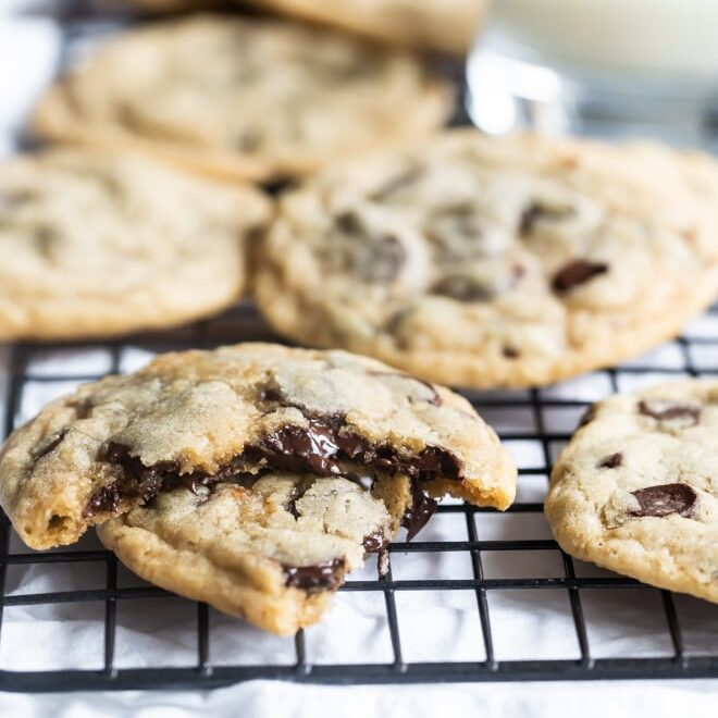 Soft chocolate chip cookies arranged in a pile on a wire rack with a glass of milk in the background.