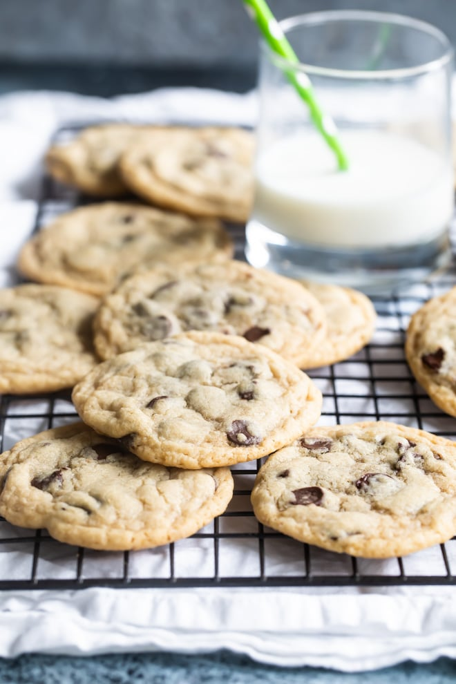Chocolate chip cookies arranged in a pile on a wire rack with a glass of milk in the background.