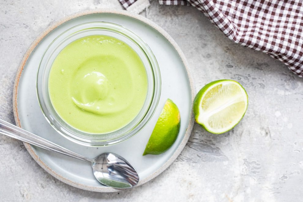 Avocado sauce in a clear bowl on a white plate with a spoon resting on it.