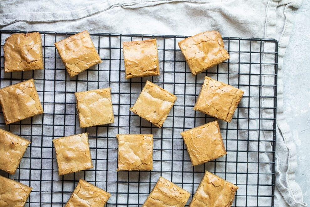 Square cut blondies on a cooling rack.