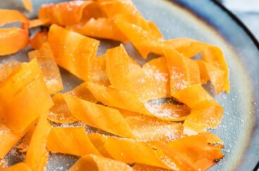 Candied carrot curls on a blue plate.