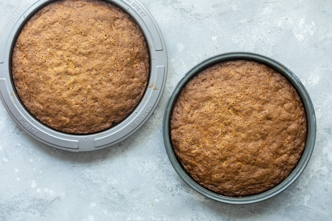 Two carrot cake layers in round baking pans.