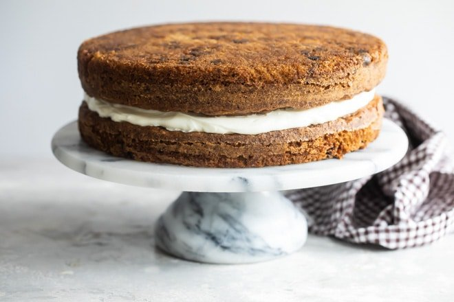 Two layers of carrot cake separated by frosting.
