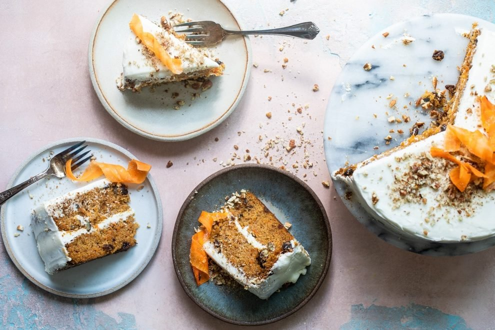 Three slices of carrot cake on plates with forks and the cake on a black and white marble platter.