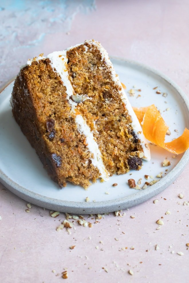 A slice of carrot cake on a blue plate.