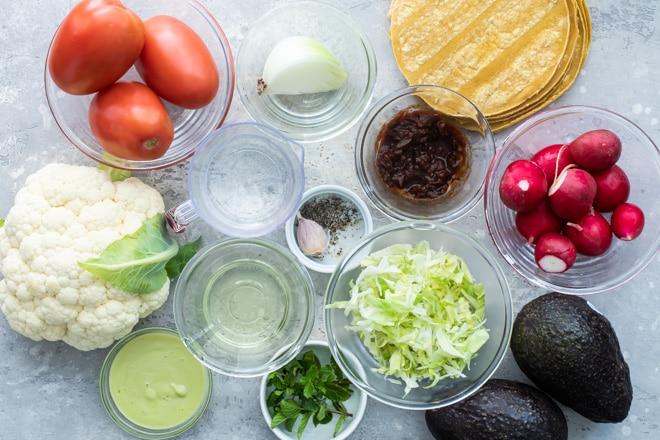 Cauliflower tinga taco ingredients in various bowls.
