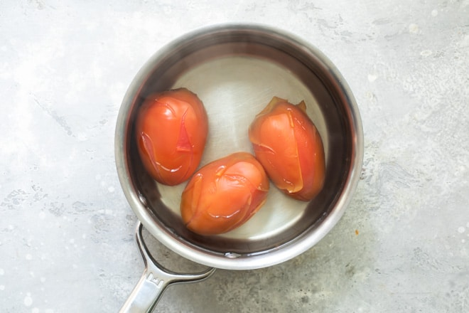 Three tomatoes in boiling water in a sliver pot.