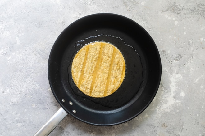A corn tortilla toasting on a black skillet.