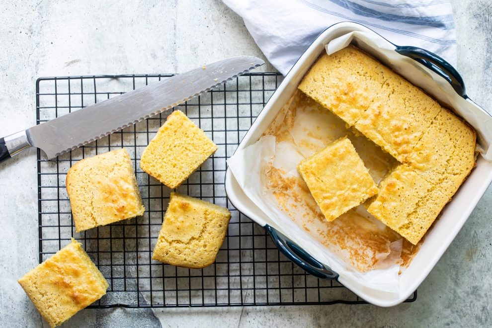 A pan of cornbread with four slices resting on a cooling rack with a bread knife.