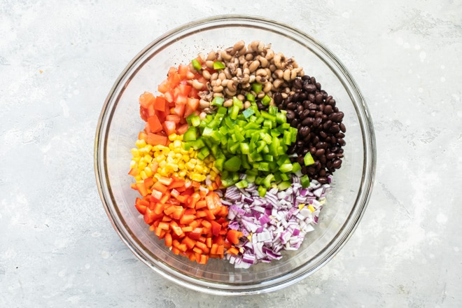 Separated cowboy caviar ingredients in a clear bowl.
