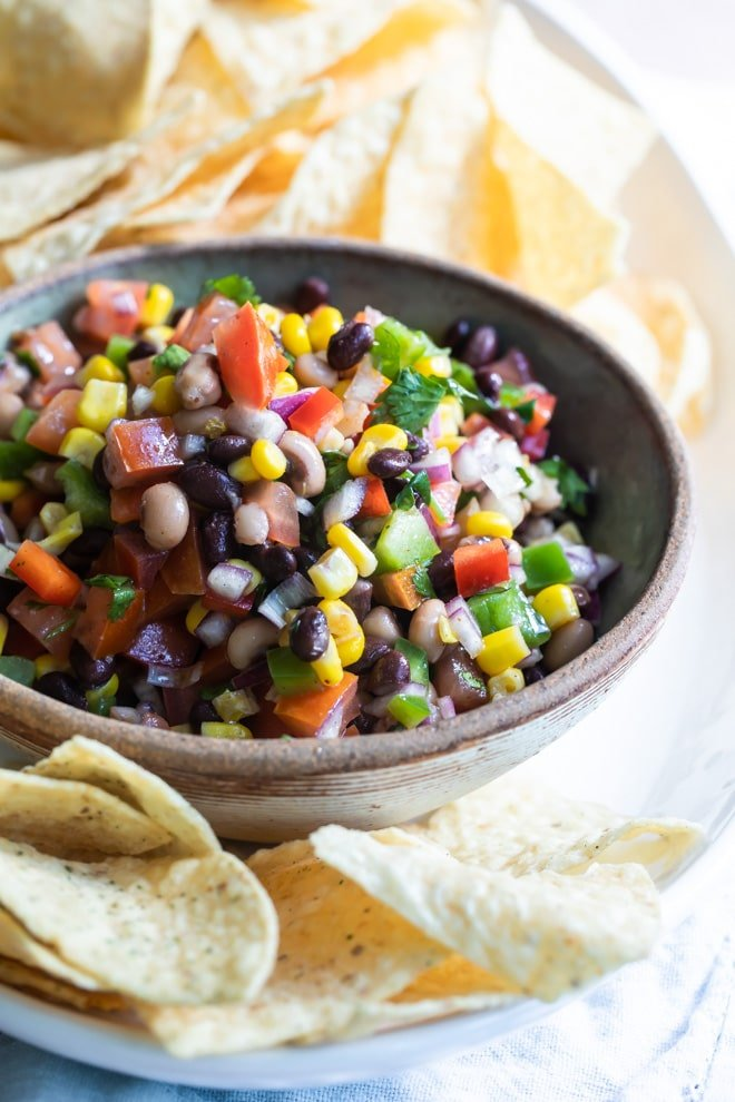 Cowboy caviar in a bowl on a white plate with tortilla chips.