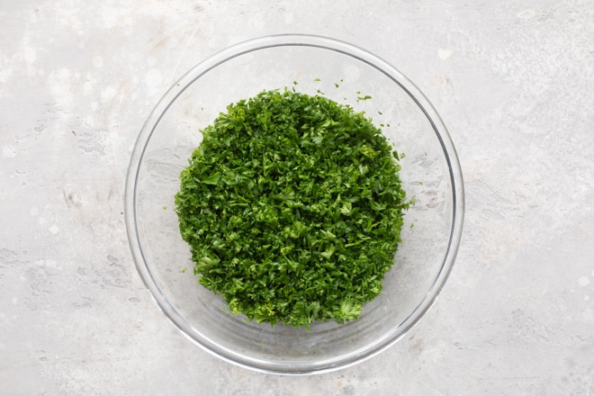 Chopped curly parsley in clear bowl.