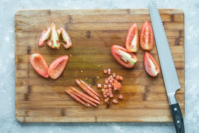 Various stages of coring and slicing a tomato.