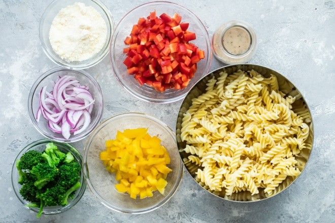 Easy cold pasta salad ingredients in various bowls.
