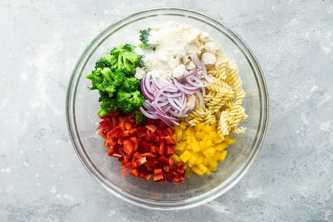 Separated easy cold pasta salad ingredients in a clear bowl.